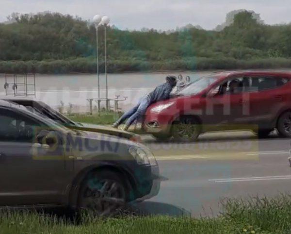 Мужчина едет на капоте автомобиля в Омске